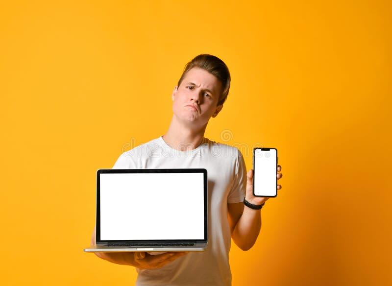 De jonge mens die een laptop computer en een mobiele smartphone, status houden toont het scherm van de telefoon en de computer in royalty-vrije stock afbeelding