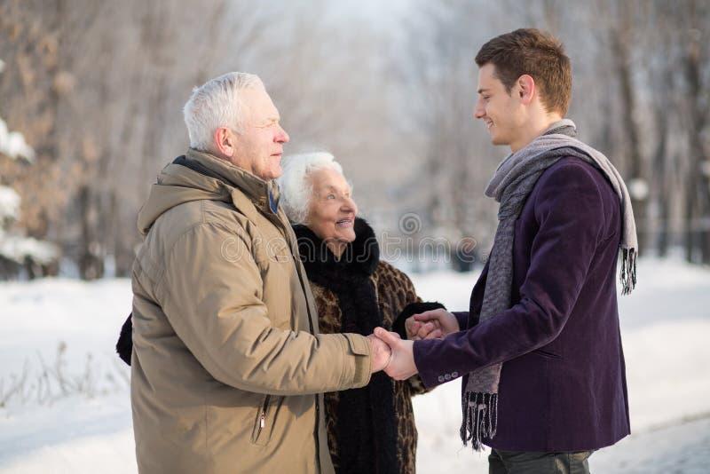 De jonge mens die een sjaal dragen begroet een bejaard paar royalty-vrije stock fotografie