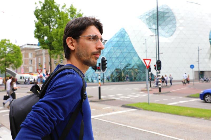 De jonge mens die met rugzak taxi?t of vervoert in Mathildelaan-hoofdstraat in Eindhoven, Nederland wachten per bus royalty-vrije stock afbeelding