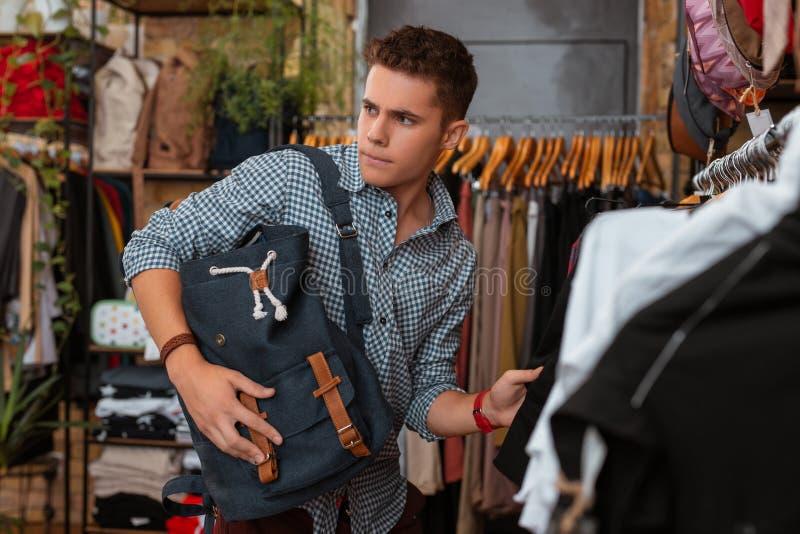 De jonge mens die met rugzak zenuwachtig terwijl het zijn in kleren winkelt voelen royalty-vrije stock afbeeldingen