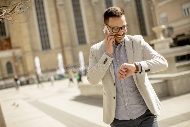 De jonge mens die mobiele telefoon met behulp van en bekijkt openlucht zijn horloge royalty-vrije stock afbeeldingen