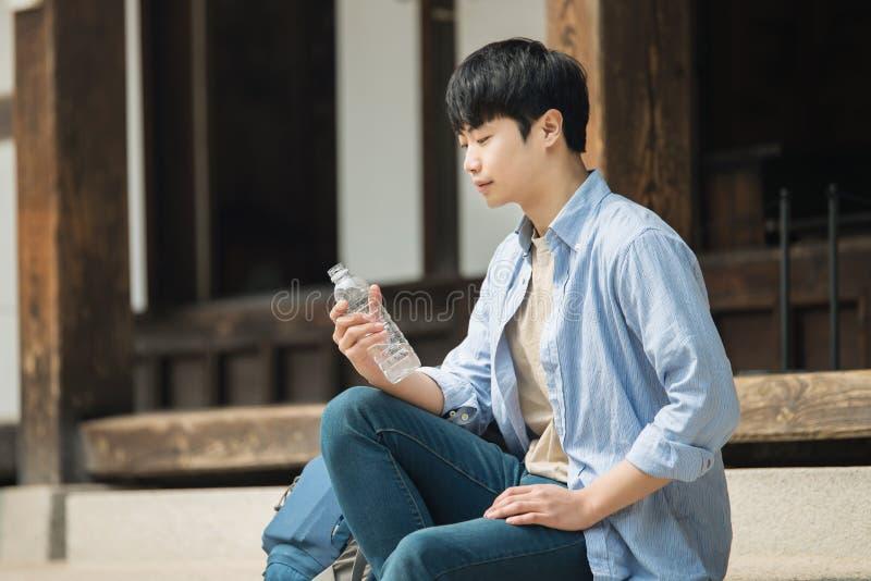 de jonge mens die naar Korea reizen neemt een rust met een water bot stock afbeelding