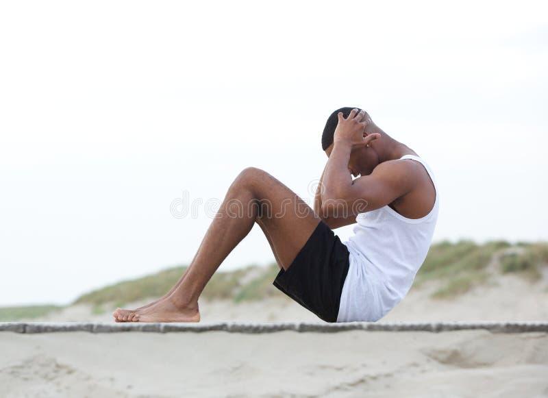 De jonge mens die op strand het doen uitoefenen zit UPS stock foto