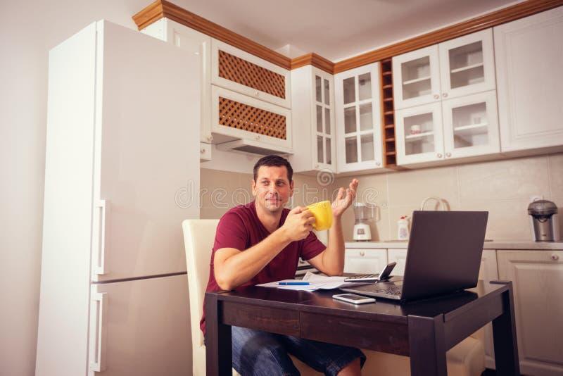 De jonge mens die rekening over uitgaven doen thuis, en drinkt koffie royalty-vrije stock foto