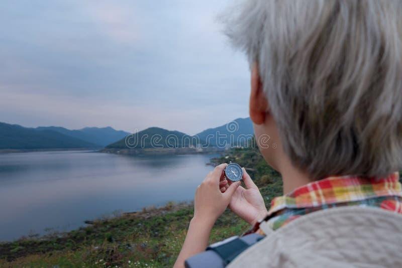 De jonge mens die trekker richting met een kompas zoeken geniet van reizend met rugzak, wandelingsconcept, reisconcept stock fotografie