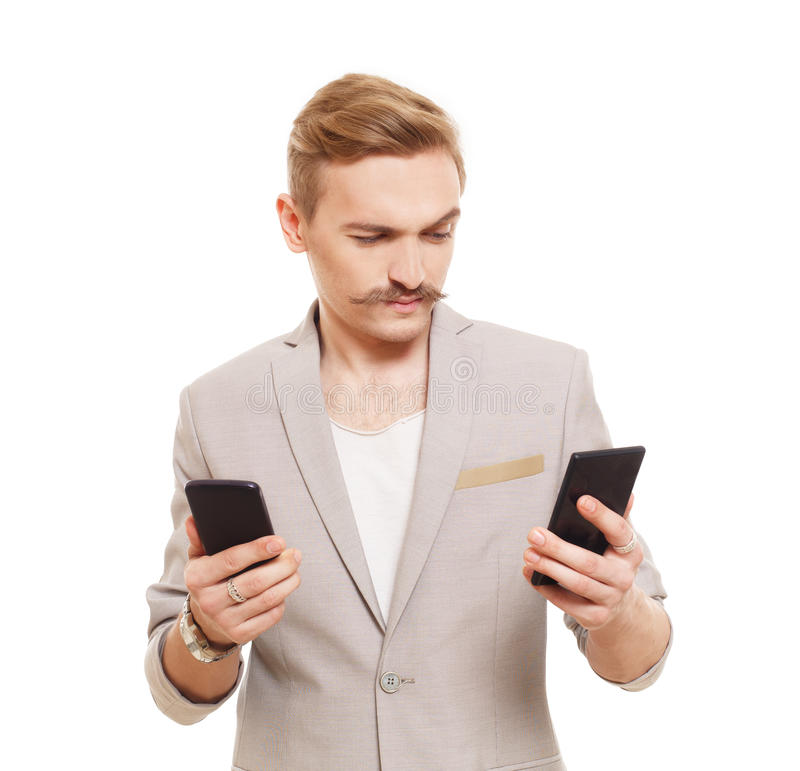 De jonge mens die twee mobiele telefoons houden, maakt keus stock afbeelding
