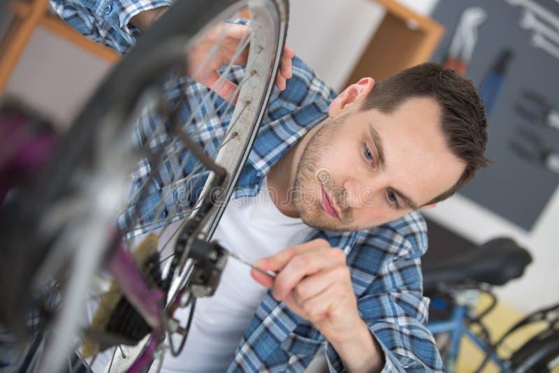 De jonge mens die van de close-upfoto fiets achterwiel herstellen royalty-vrije stock afbeeldingen
