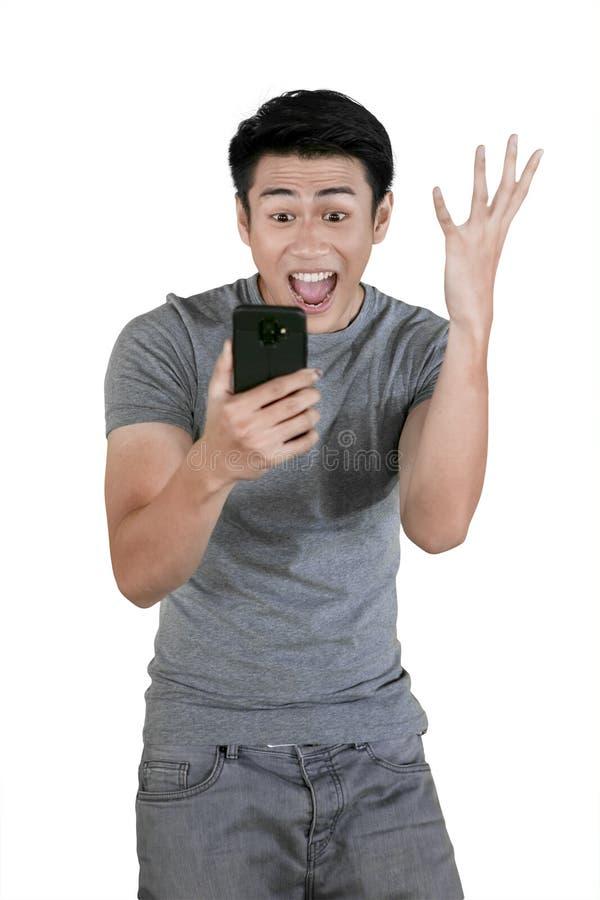 De jonge mens drukt succes tijdens greep uit een telefoon stock afbeelding
