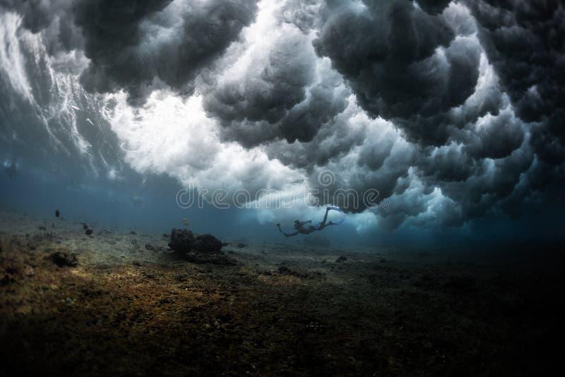 De jonge mens duikt onder de krachtige oceaangolf royalty-vrije stock afbeeldingen