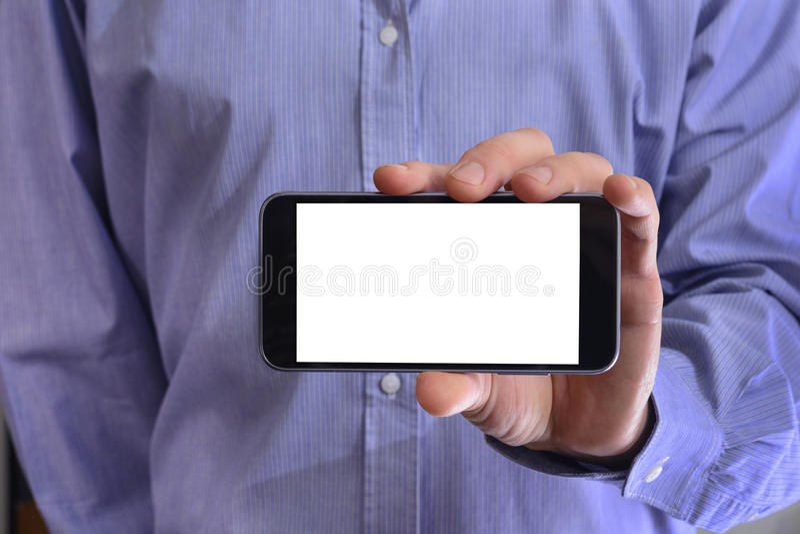 De jonge mens in een blauw overhemd houdt een telefoon met witte scre royalty-vrije stock afbeeldingen