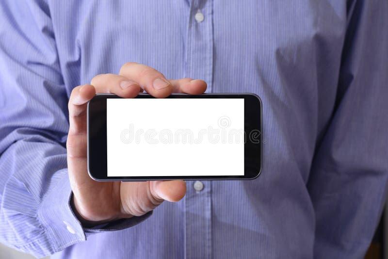 De jonge mens in een blauw overhemd houdt een telefoon met witte scre royalty-vrije stock fotografie