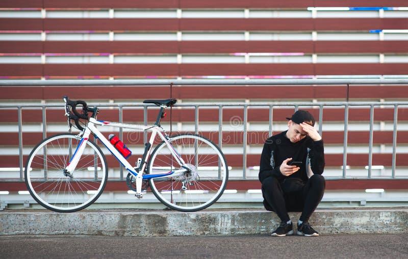 De jonge mens in een donkere sport draagt een fiets op een gestreepte achtergrond van Bourgondië en gebruikt een smartphone stock afbeeldingen