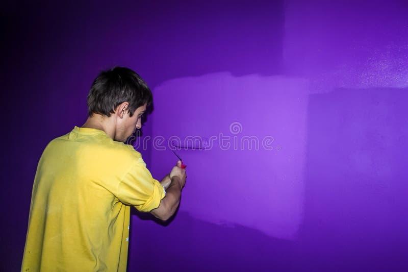 De jonge mens in een geel overhemd met een rol schildert de muur stock afbeelding