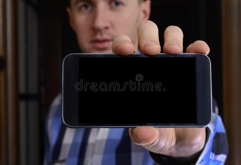 De jonge mens in een geruit blauw overhemd houdt een telefoon met royalty-vrije stock foto's