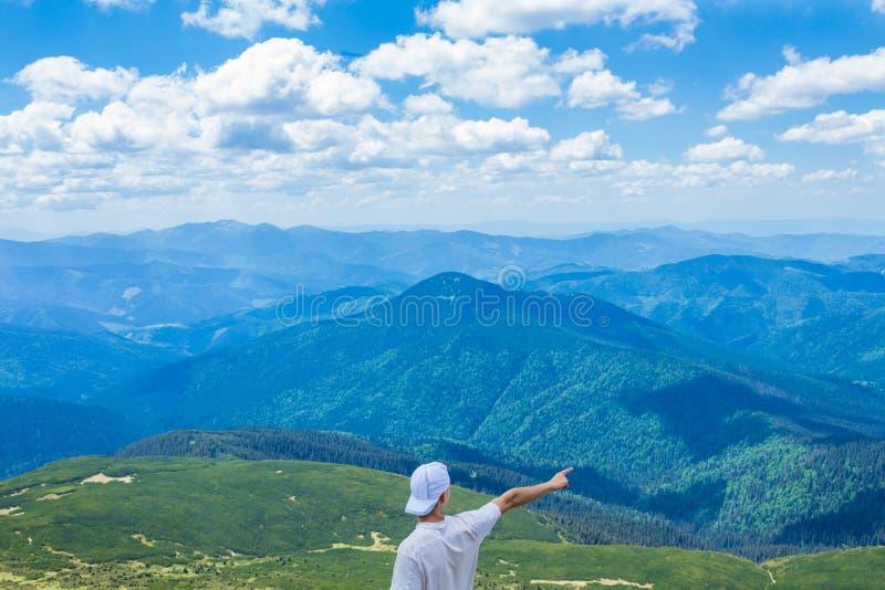 De jonge mens in een GLB bevindt zich bij de piek van de berg met een mooie mening van de bergen en de wolken royalty-vrije stock foto's