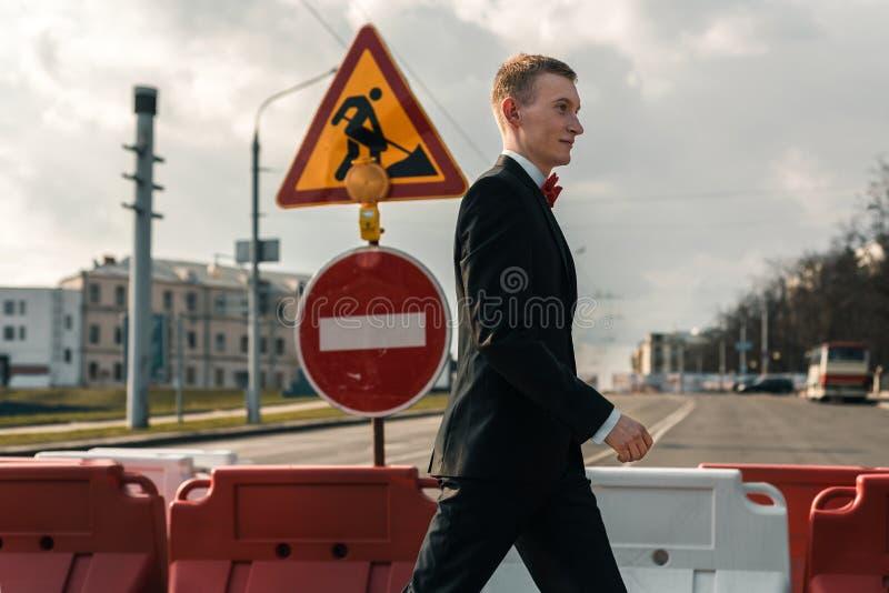De jonge mens in een kostuum loopt langs een voetgangersoversteekplaats Op de verkeersteken is in aanbouw stock fotografie