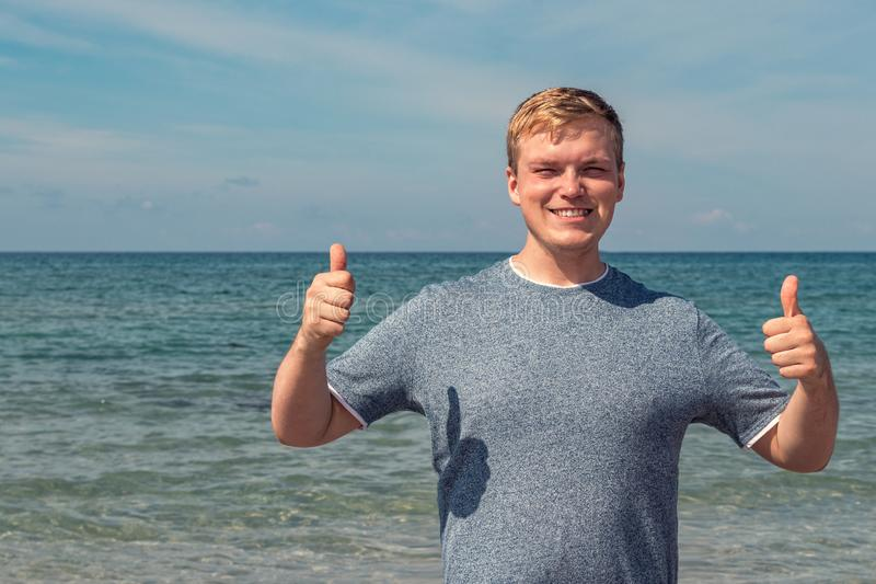 De jonge mens in een t-shirt op de kust en bekijkt het overzees, achtermening royalty-vrije stock afbeelding