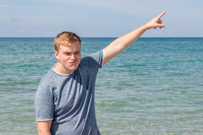 De jonge mens in een t-shirt op de kust en bekijkt het overzees, achtermening stock foto's