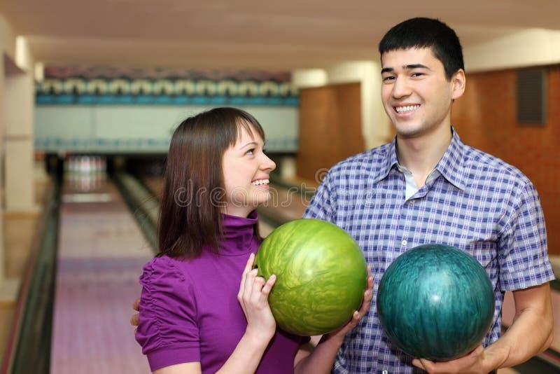 De jonge mens en het meisje houden ballen en lach royalty-vrije stock afbeelding