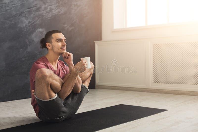 De jonge mens in flexibele yoga stelt het drinken thee royalty-vrije stock fotografie