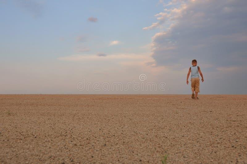 De jonge mens gaat in zandwoestijn uit royalty-vrije stock afbeeldingen