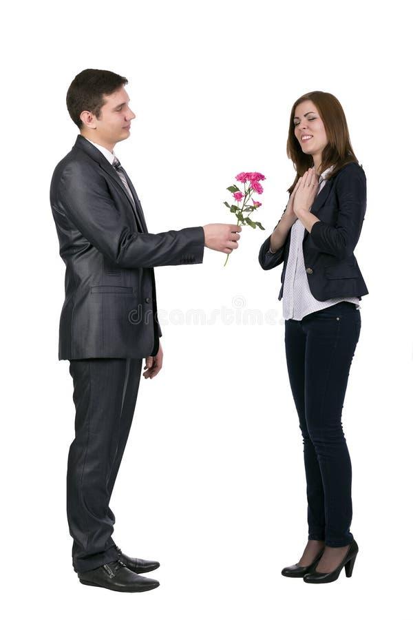 De jonge mens geeft een tak van bloemen aan mooi stock afbeelding