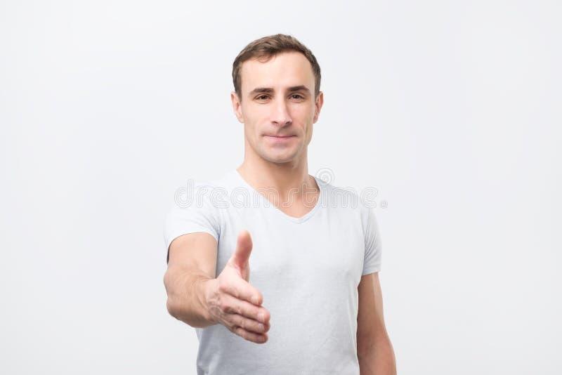 De jonge mens geeft handdruk, begroet met iemand, verheugt zich vergadering stock foto