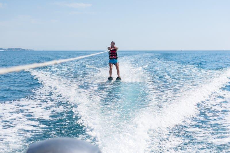 De jonge mens glijdt op water ski?end op de golven op het overzees, oceaan Gezonde Levensstijl Positieve menselijke emoties, vreu stock foto