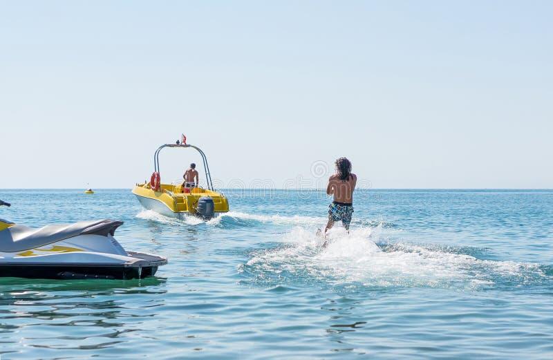 De jonge mens glijdt op water ski?end op de golven op het overzees, oceaan Gezonde Levensstijl Positieve menselijke emoties, gevo royalty-vrije stock foto's