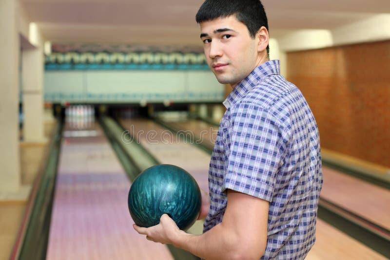 De jonge mens houdt bal voor kegelen stock afbeelding