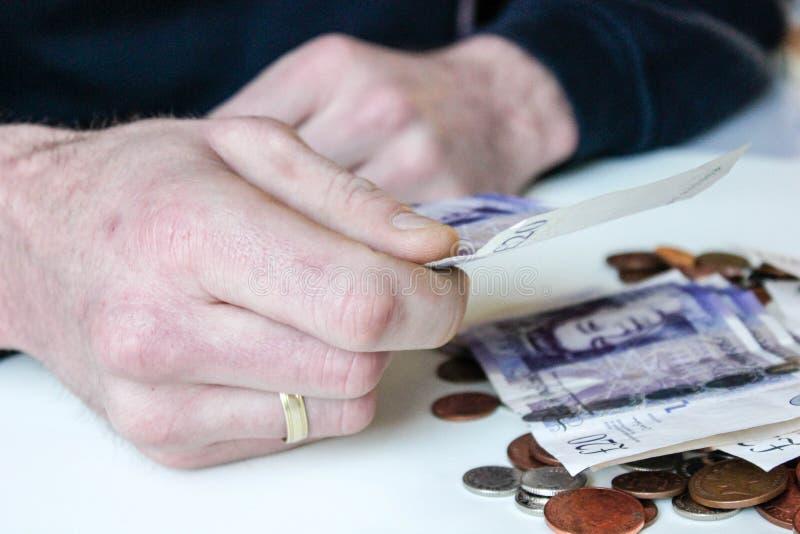 De jonge mens houdt GBP twintig van de geldponden nota en de muntstukken zijn liyng rond op een lijst royalty-vrije stock afbeelding