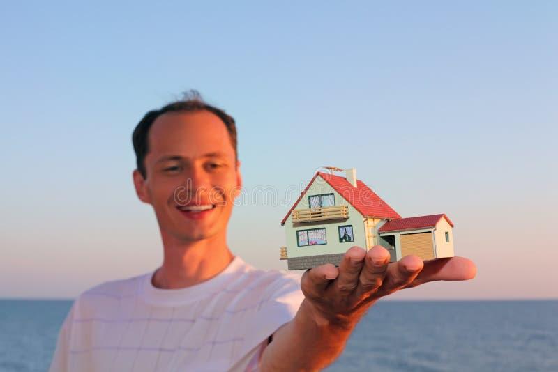 De jonge mens houdt in hand model van huis met garage stock foto
