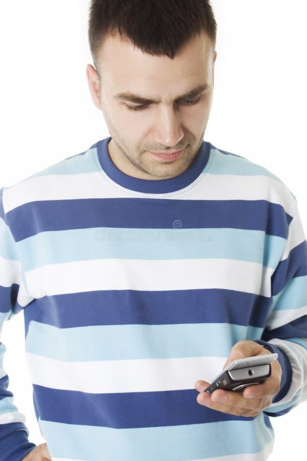 De jonge mens las een bericht op de celtelefoon royalty-vrije stock afbeeldingen