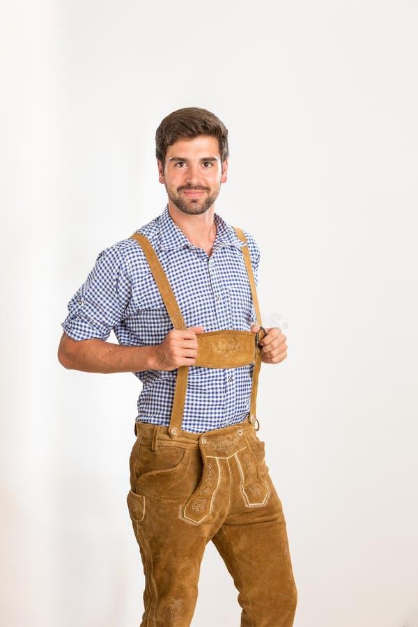 De jonge mens in leerbroek houdt zijn bretels stock foto's