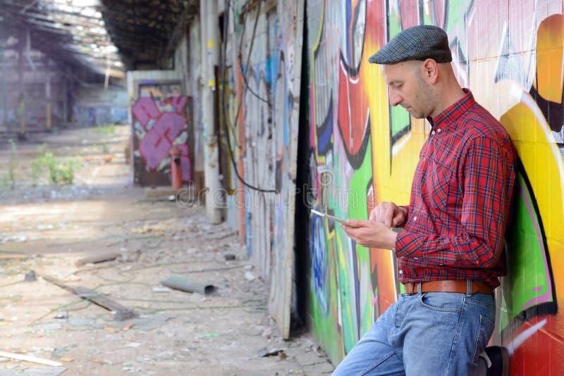 De jonge mens leunt tegen een graffitimuur stock afbeelding