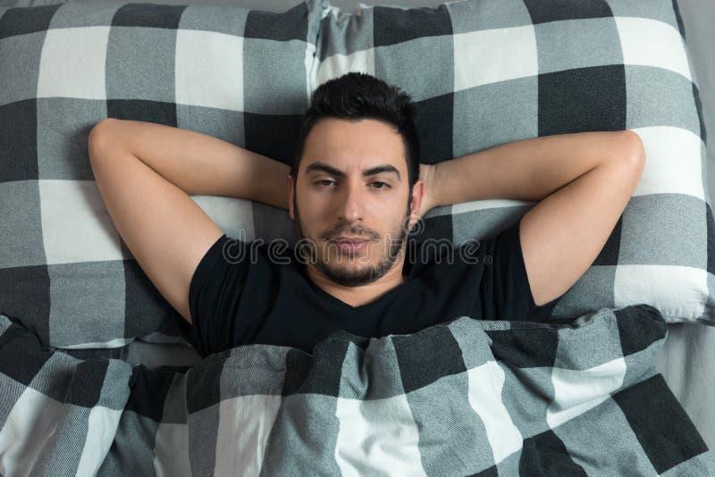 De jonge mens ligt in bed Hij is gelukkig, bekijkt de camera royalty-vrije stock fotografie
