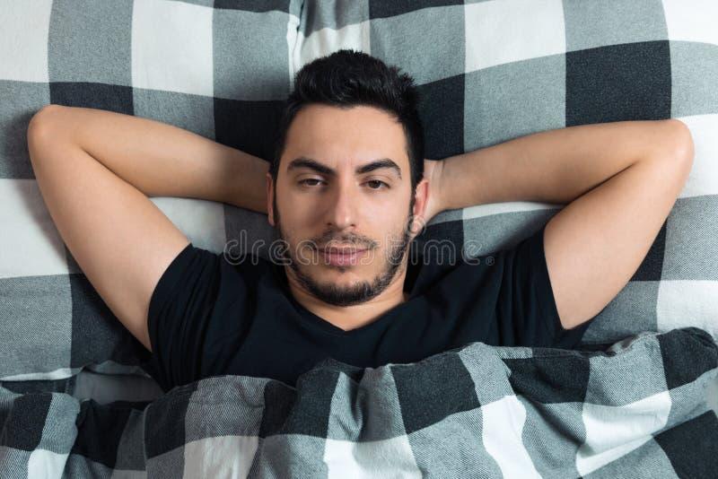 De jonge mens ligt in bed Hij is gelukkig, bekijkt de camera royalty-vrije stock afbeeldingen