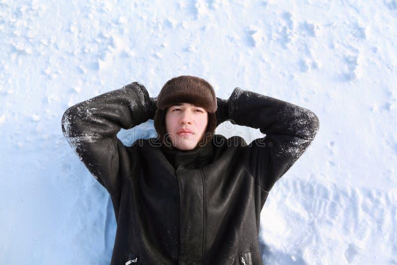 De jonge mens ligt op terug op sneeuw royalty-vrije stock afbeelding