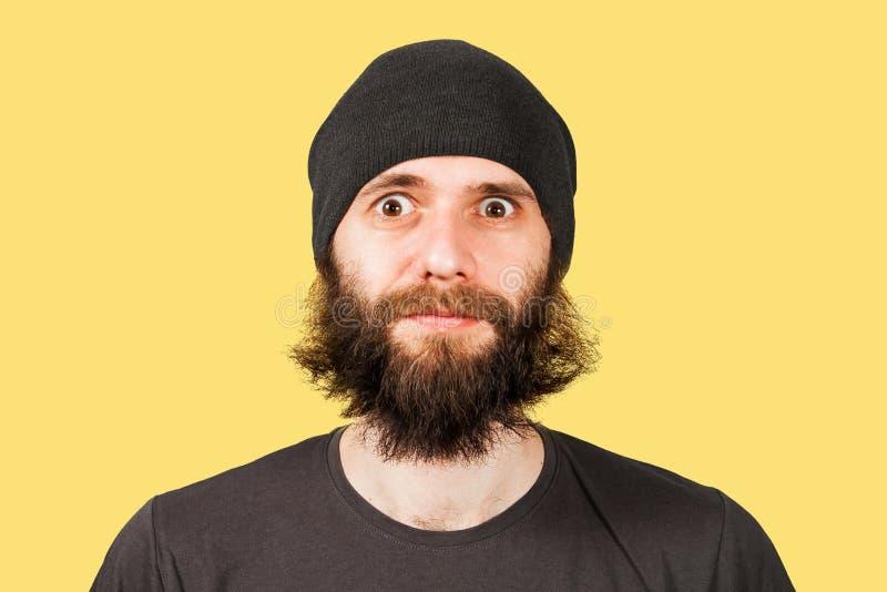 De jonge mens met baard in hoed kijkt in camera van wijd open ogen Ge?soleerd op gele achtergrond royalty-vrije stock foto