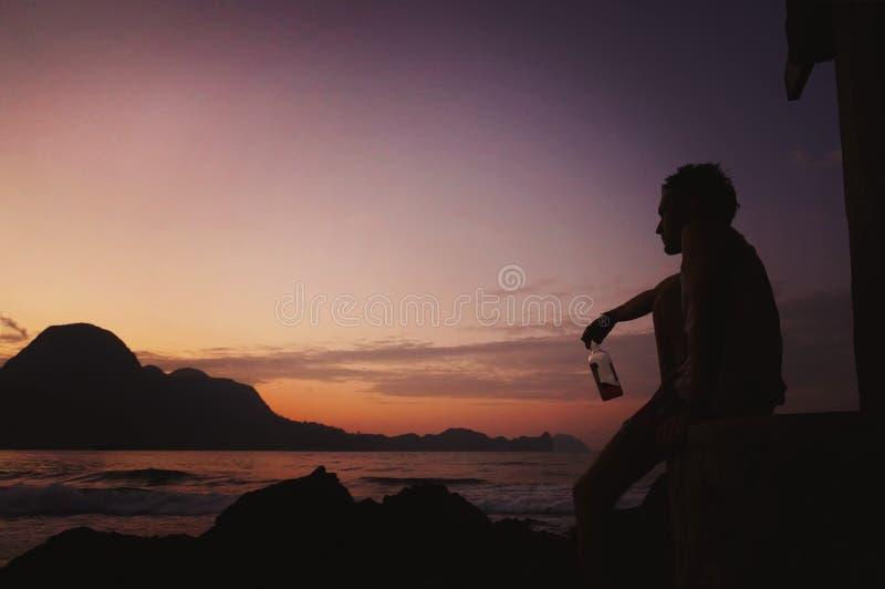 De jonge Mens met een Bier zit bij Kust op Zonsondergangachtergrond Een mens drinkt een sterke whisky en bekijkt de zonsondergang stock fotografie