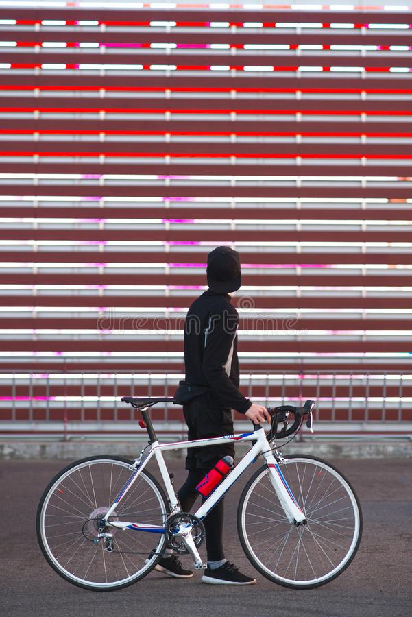 De jonge mens met een fiets en een atletische kleding is op een abstracte rode achtergrond royalty-vrije stock afbeeldingen