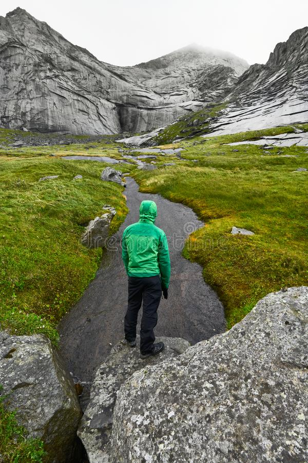 De jonge mens met een groene jasje en een kap bevindt zich met zijn rug op een rots voor een reusachtige berg op Lofoten-Eilanden royalty-vrije stock afbeeldingen