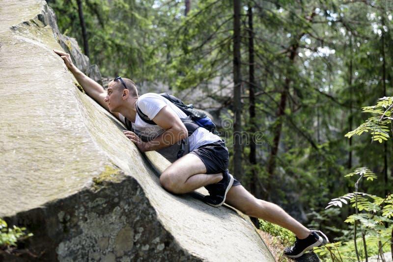 De jonge mens met een rugzak beklimt op de klip in het naald bosclose-up stock fotografie