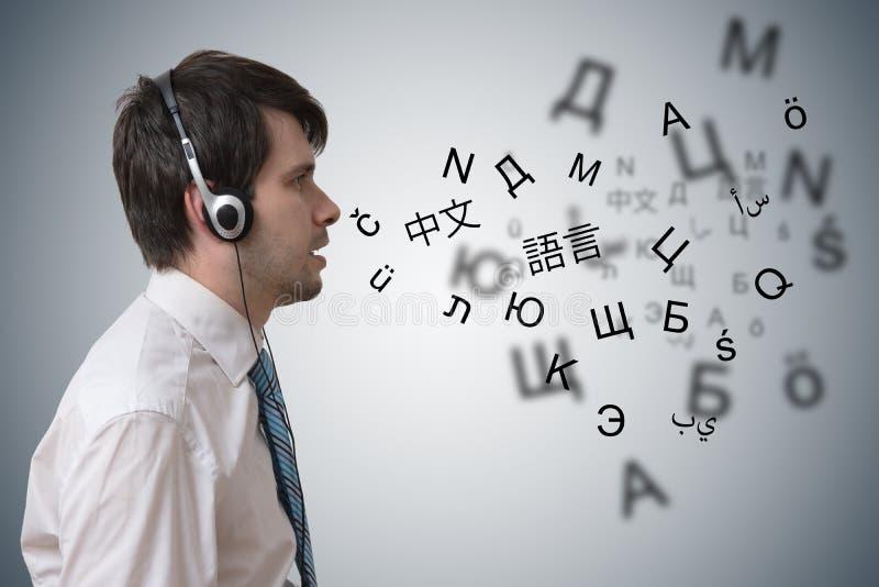 De jonge mens met hoofdtelefoons leert verschillende vreemde talen stock foto's
