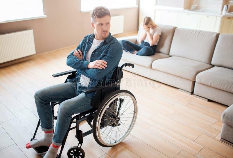De jonge mens met inclusiviteit en de onbekwaamheid zitten op rolstoel vooraan Overhandigt gekruist en verstoord De jonge vrouw z royalty-vrije stock foto
