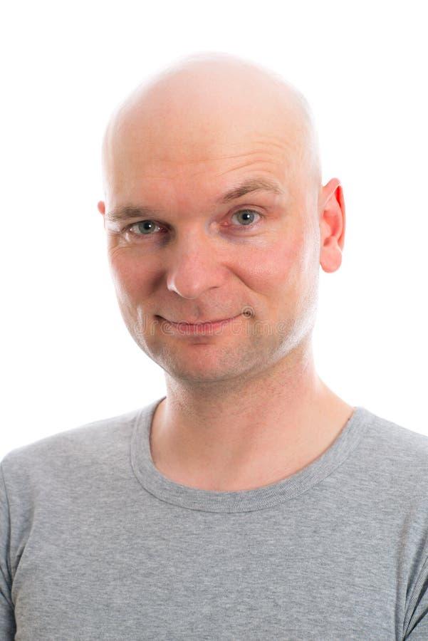 De jonge mens met kaal hoofd glimlacht binnen aan de camera stock afbeelding