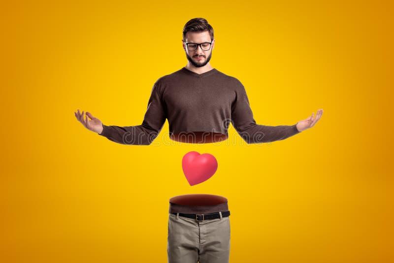 De jonge mens met lichaam sneed in twee bij taille, hoger lichaam in lucht, met leuk rood valentijnskaarthart die tussen bovenlee royalty-vrije stock foto