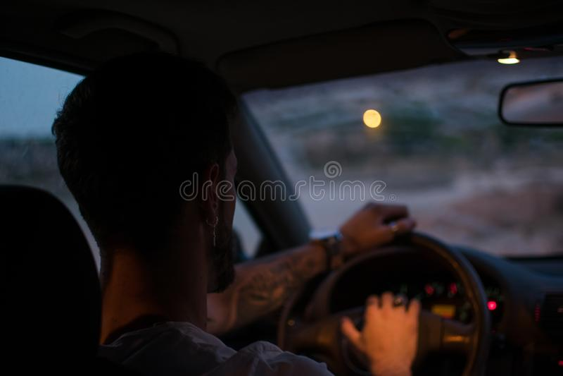De jonge mens met oorringen drijft een auto bij nacht stock afbeeldingen