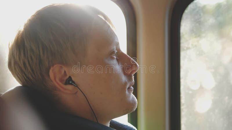 De jonge mens met smartphoneritten vervoert het luisteren aan muziek per bus en de zon glanst stock fotografie