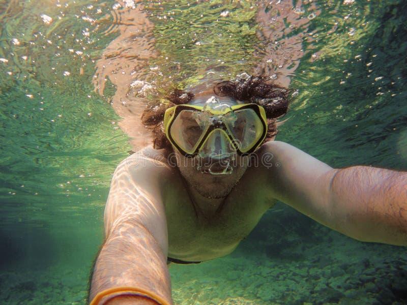 De jonge mens met snorkelen en het duiken het masker die en een selfie zwemmen nemen onder water Reis, vakantie en van de sporten stock fotografie
